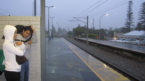Two commuters cower under the shelter at Cottesloe Train Station as the rain pours down.